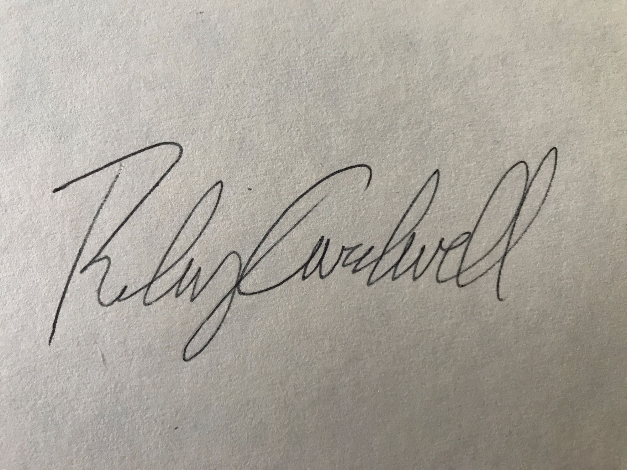 A photo of the author's signature on white paper.