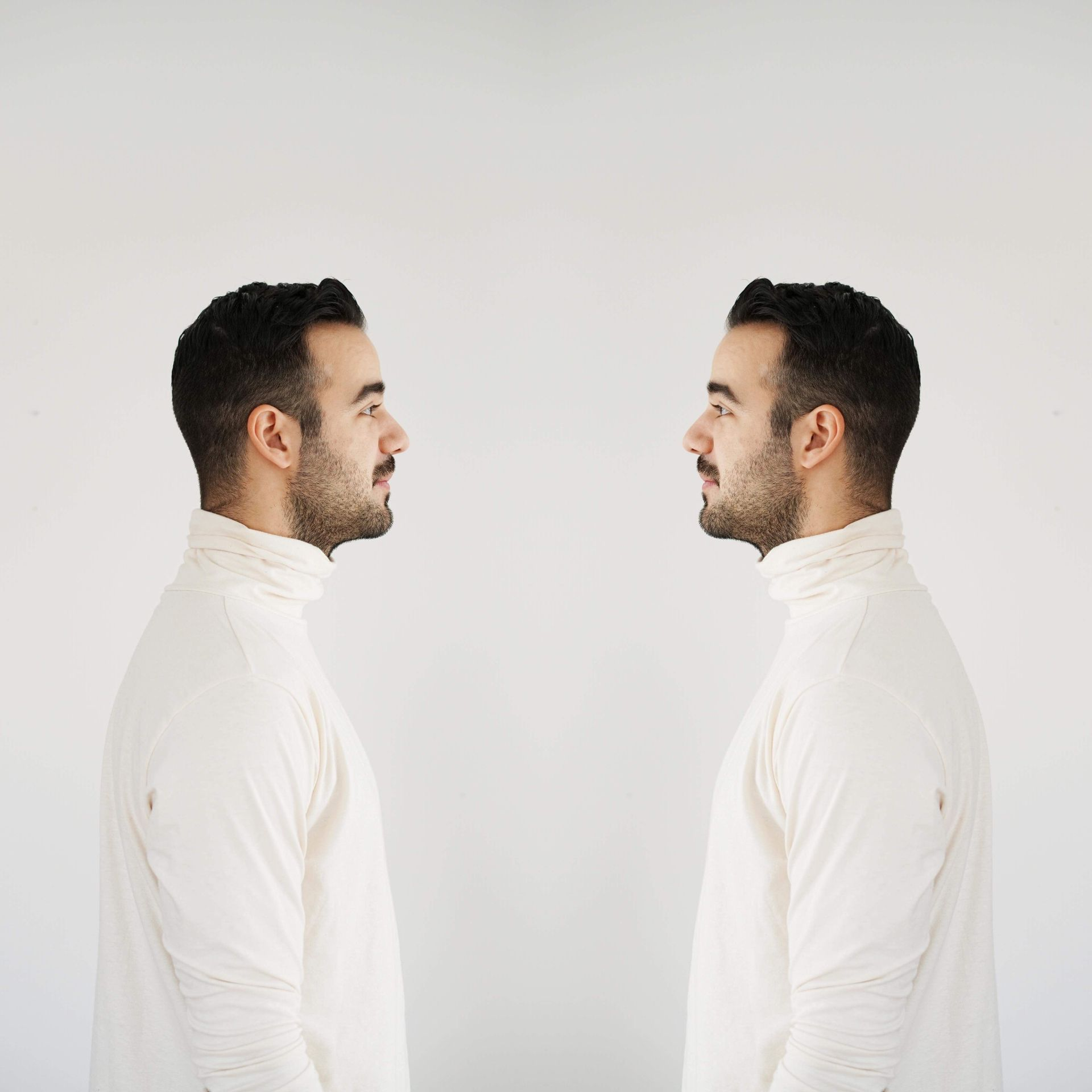 mirror image effect on a portrait of the side profile of man with brown hair wearing a white sweater