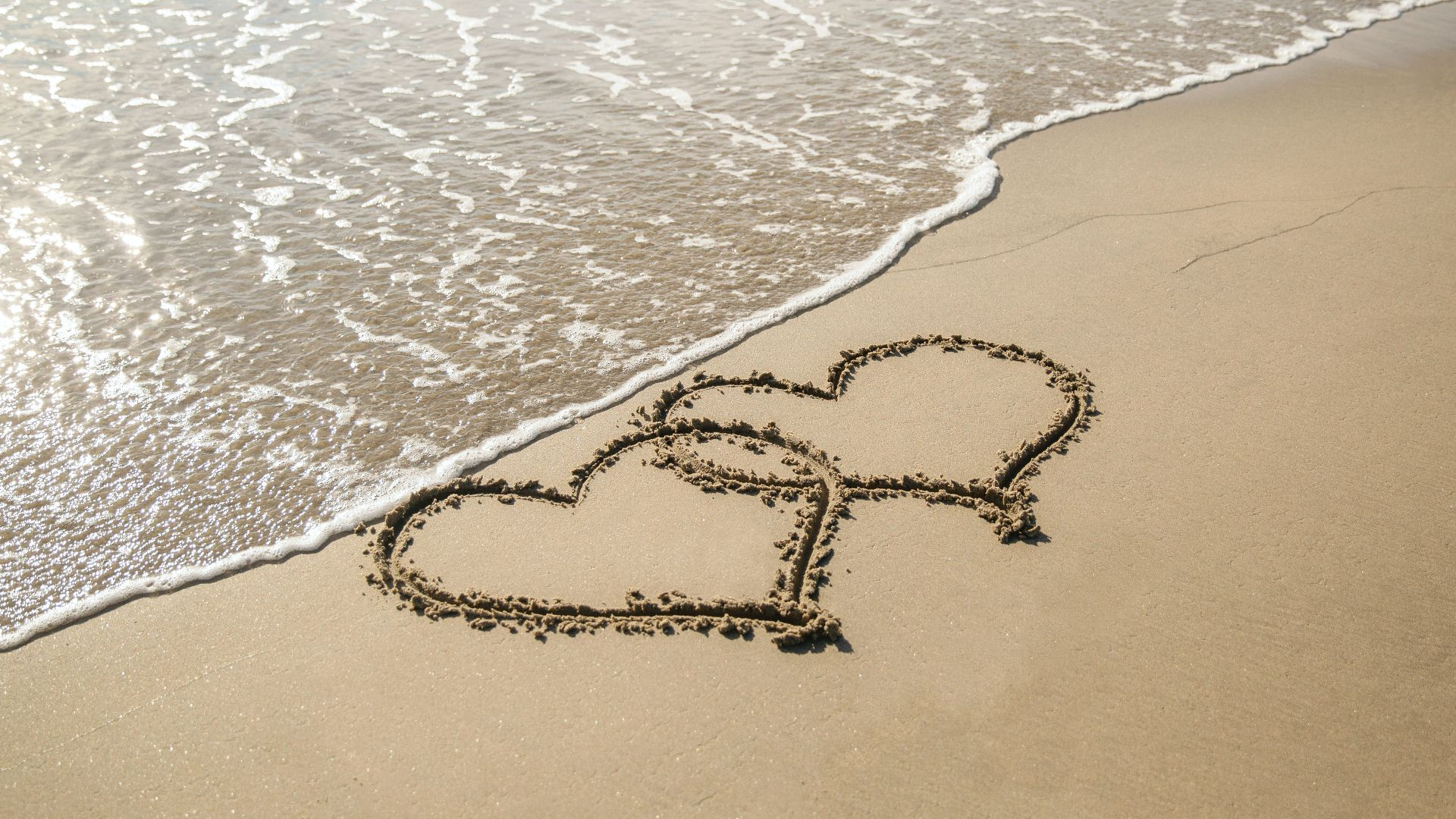 beach with two overlapping hearts drawn in the sand